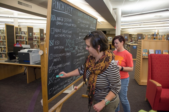 Julia McConnell, left, and Angel Suhrstedt check off the punch list before Monday's opening of the Edmond Public Library.