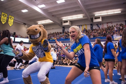 Kendall McDaniel, a cheerleader with the University of Central Oklahoma, dances with the school's mascot.
