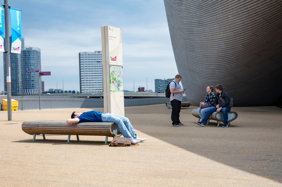 Ryan resting on a park bench in front of the Olympic Aquatic Center.jpg