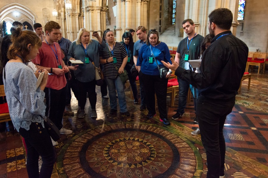 Students stand around at the Christ Church Cathedral and listen to the tour guide discuss the stone work on the floor