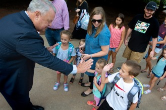 Bret Towne, Edmond Schools Supertindent, gives Owen Gambill a high-five on her first day of second grade.