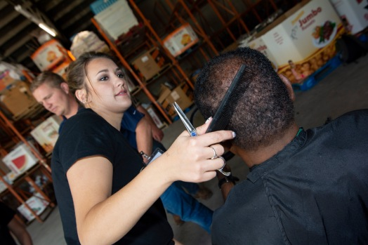 Brooke Slabbekoorn, hairstylist with Hello Love, cuts Reggie Jones's hair, 67 and transportation worker for the Jesus House